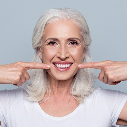 Woman pointing to implant-retained denture.