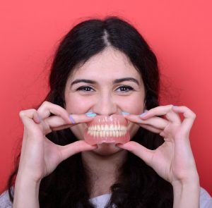 woman smiling holding dentures