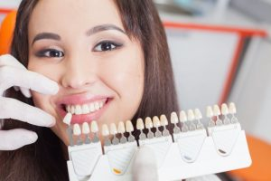 woman smiling beside porcelain veneer samples