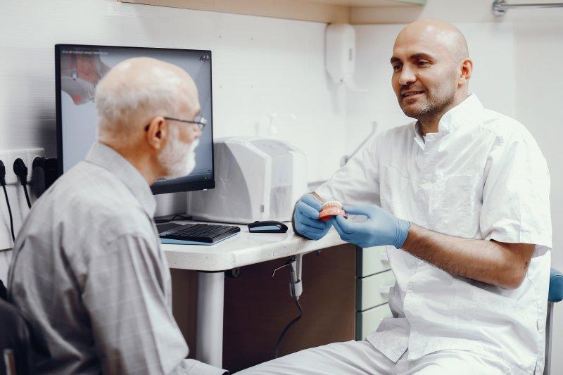 Dentist explaining how denture adhesive works